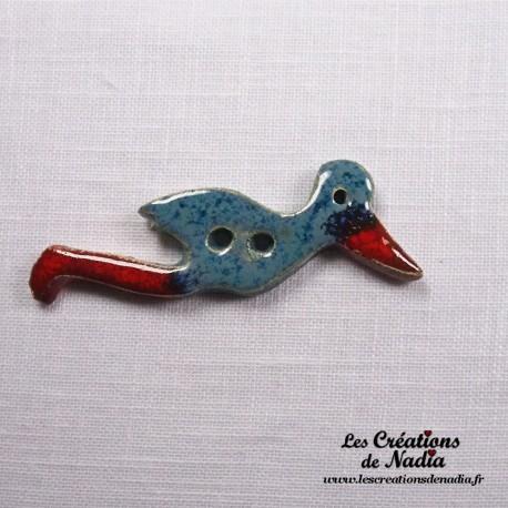 Bouton cigogne en vol bleu